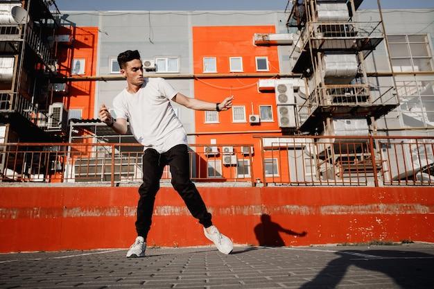 청바지와 티셔츠를 입은 젊은 남자가 따뜻한 날 도시 건물을 배경으로 거리에서 현대 무용을 추고 있습니다.
