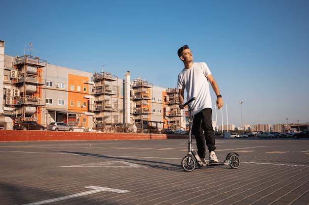 청바지와 티셔츠를 입은 젊은 남자가 화창한 날 건물 근처에 주차하기 위해 광장에서 스쿠터를 타고 있습니다.