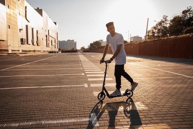 청바지와 티셔츠를 입은 젊은 남자가 화창한 날 건물 근처에 타일로 포장된 광장에서 스쿠터를 타고 있습니다.