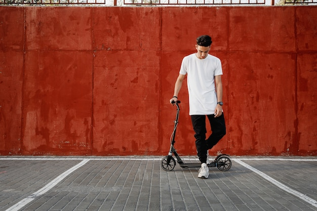 Молодой парень в джинсах и футболке стоит со скутером у окрашенной бетонной стены в летний день в городе. .