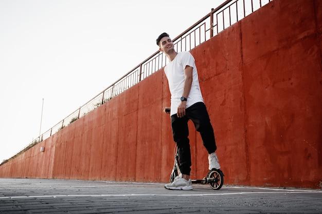 청바지와 티셔츠를 입은 젊은 남자는 도시의 여름날 페인트 칠한 콘크리트 벽에 스쿠터를 들고 서 있습니다. .