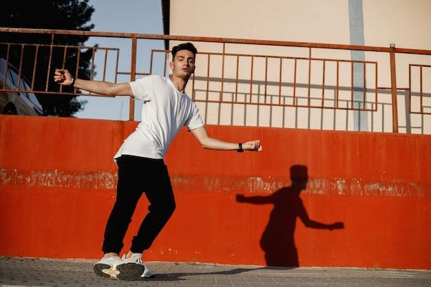 청바지와 흰색 티셔츠를 입은 젊은 남자가 화창한 날 페인트 칠한 콘크리트 벽에 기대어 거리에서 현대 무용을 추고 있습니다.