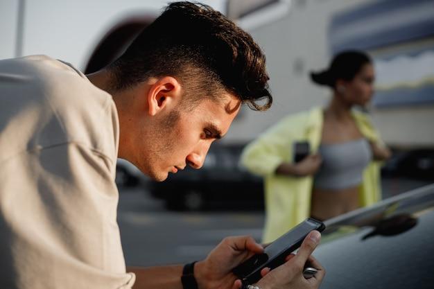 흰색 티셔츠를 입은 젊은 남자가 화창한 날 주차하기 위해 광장에 있는 여자 옆에 전화를 사용하고 있습니다.