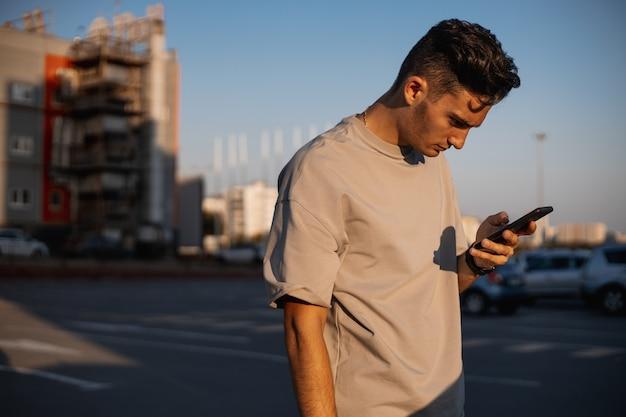 흰색 티셔츠를 입은 젊은 남자가 화창한 날 주차를 위해 광장에서 전화를 사용하고 있습니다.