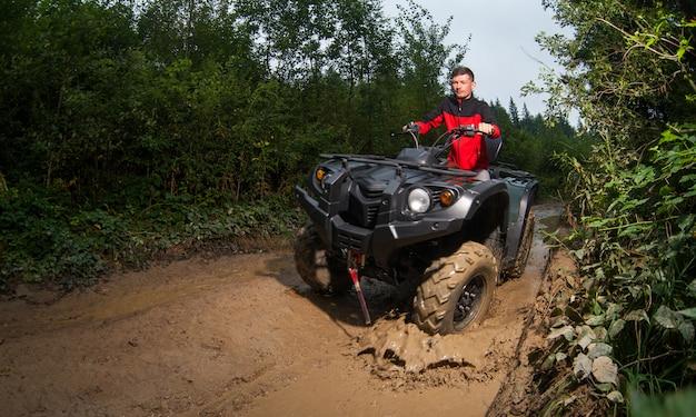 Young guy driving four-wheeler atv through mud