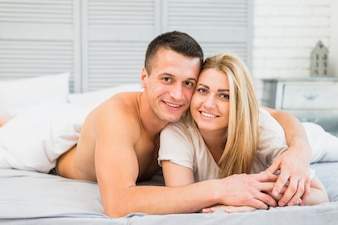 Young guy embracing attractive happy lady in bed