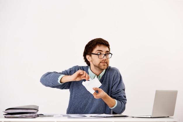 Молодой парень, сотрудник, ведущий себя сумасшедшим на работе, сидит за офисным столом, разрывает документы, чувствует себя напряженным, выгорает на работе, смотрит в сторону безумным
