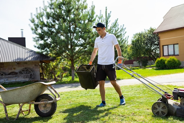 Young guy empties the grass catcher of the lawn mower