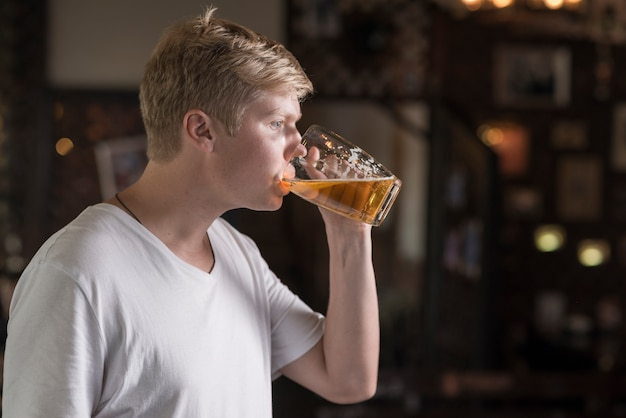 Young guy enjoying beer in pub