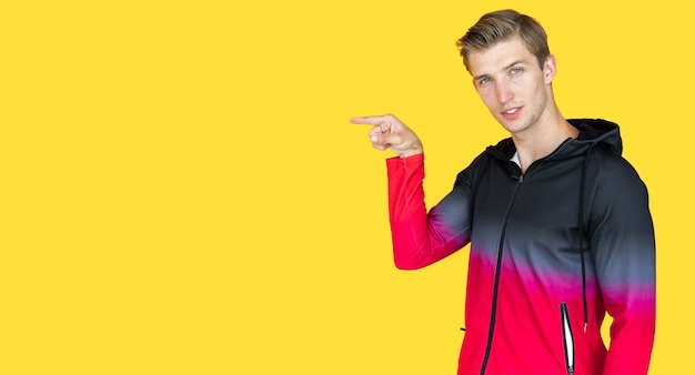 Young guy of european appearance on a yellow background. point your finger at an empty spot. copy space