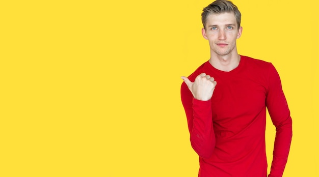 Young guy of european appearance on a yellow background. the thumb points to an empty space. copy space