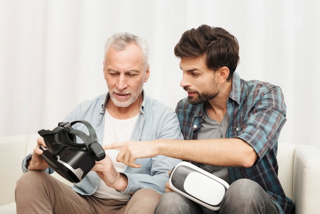 Young guy explaining to aged man about vr glasses on sofa