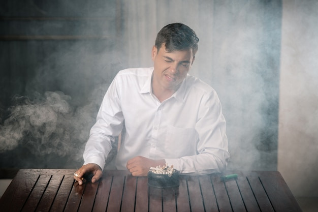 Young guy fending off tobacco smoke, sitting at a table on which stands a full ashtray, holding a lit cigar in his hand. the terrible consequences of cigarette smoke.