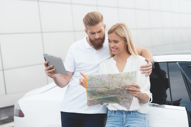 A young guy and a girl are looking at a map of highways.