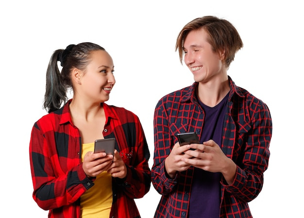 A young guy and a girl in plaid shirts stand side by side and look at each other with a smile, holding their smartphones in their hands isolated on white background