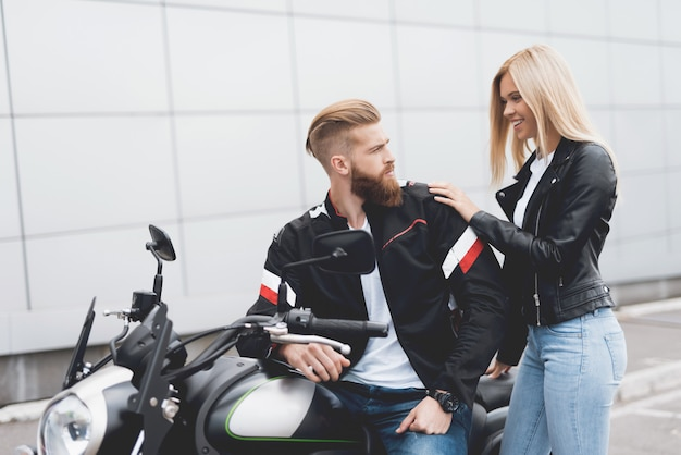 Young guy and girl sitting on a modern electric motorcycle