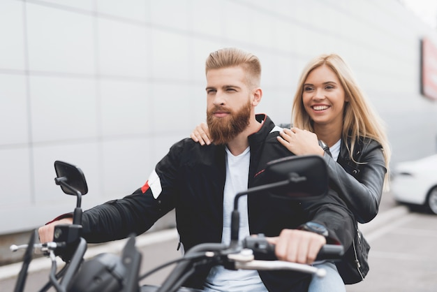 Young guy and girl sitting on a modern electric motorcycle.
