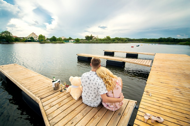A young guy and a girl on a wooden pier