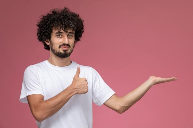 Молодой парень показывает пустую руку и показывает палец вверх