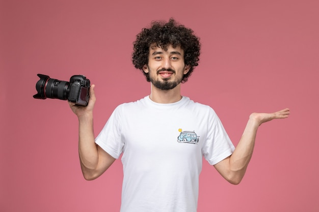 Young guy giving pose with empty hand and photocamera