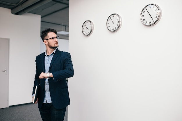 Young guy in glasses is  walking in office. he wears blue shirt, dark jacket, jeans and beard. he holds  laptop in hand. he is looking to clock on wall.
