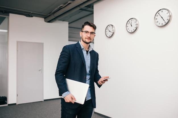 Il giovane ragazzo con gli occhiali sta camminando in ufficio. indossa camicia blu, giacca scura, jeans e barba. tiene in mano telefono e laptop. guardando alla telecamera.