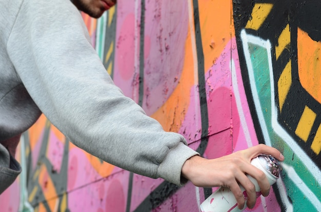 A young guy in a gray hoodie paints graffiti in pink and green c
