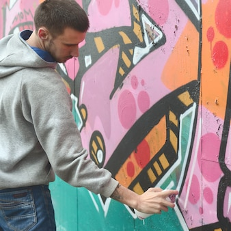 A young guy in a gray hoodie paints graffiti