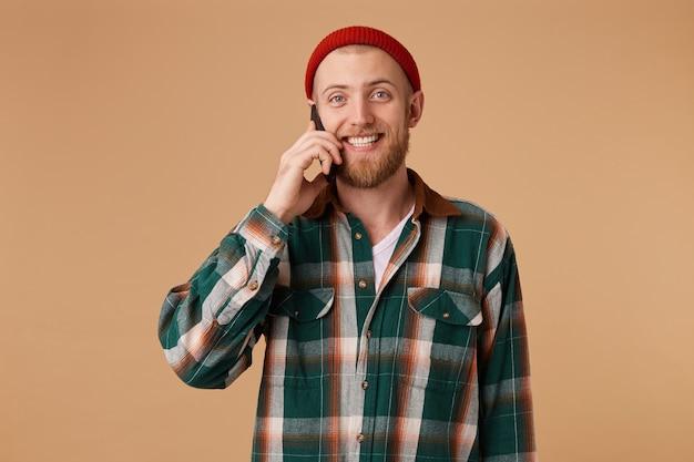 若い男は楽しい電話での会話をしています