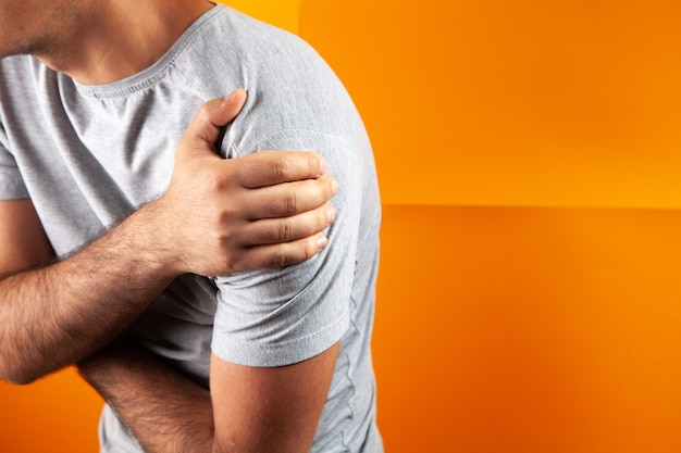 A young guy has a shoulder ache on an orange background