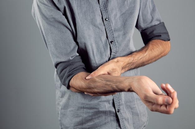 Young guy has a sore arm on a gray background