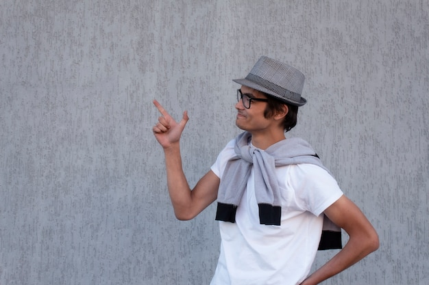 Young guy in a hat and glasses showing thumbs up on concrete.