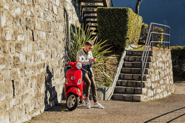 Молодой парень держит мобильный телефон на красном мотоцикле.