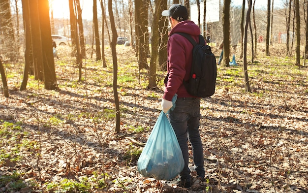 The young guy holding big plastic bag with trash in the forest