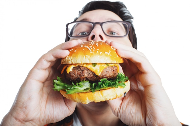 A young guy holding a fresh burger.