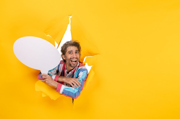 白い風船を持って、黄色い紙の引き裂かれた穴と自由な背景で笑っている若い男