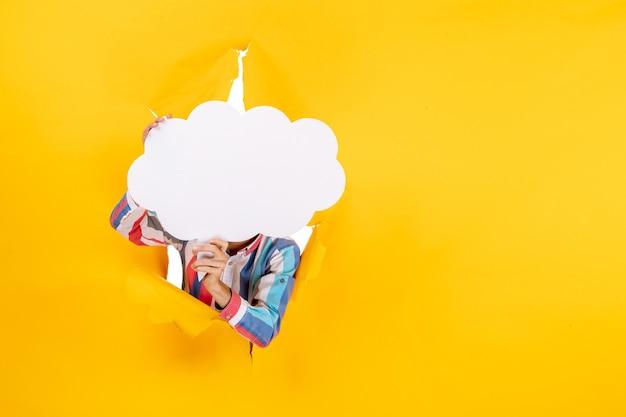 彼の顔の前に白い雲の形の紙を保持し、引き裂かれた穴と黄色い紙の自由な背景でカメラのポーズをとる若い男