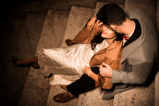 Young guy hugging and kissing elegant lady sitting on steps