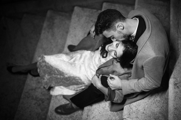 Young guy hugging and kissing happy elegant lady sitting on steps