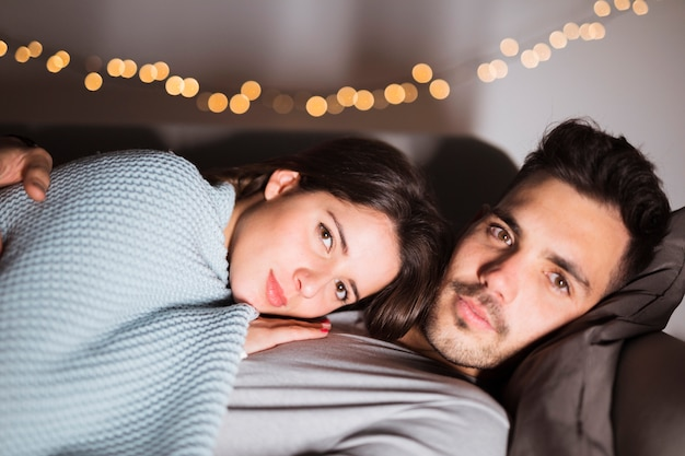 Young guy hugging lady, lying on sofa and watching tv