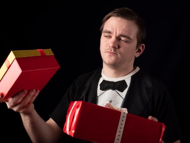 Молодой парень в черном костюме-футболке выбирает подарки на черном