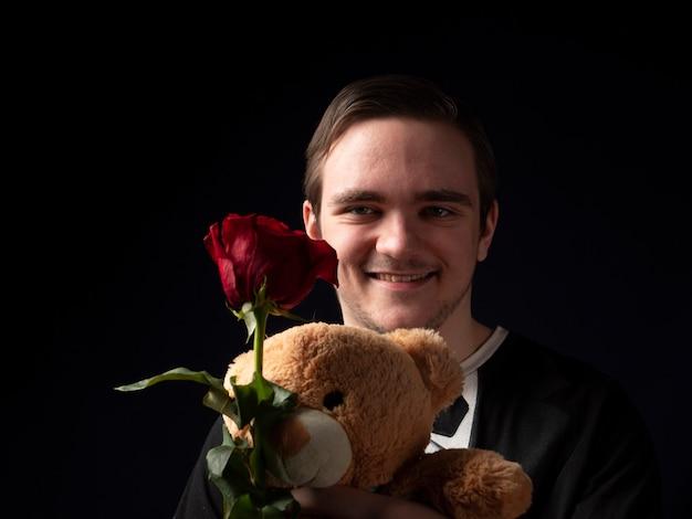 赤いバラとテディベアを手に黒いtシャツのスーツを着た若い男
