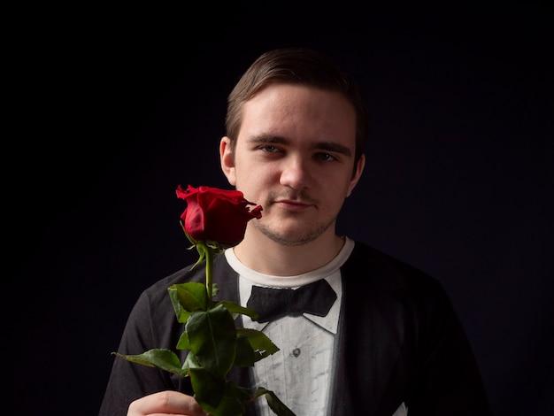 검은 색 티셔츠 정장을 입은 젊은 남자가 그의 손에 빨간 장미를 들고 검정색 배경에 미소를 짓습니다.