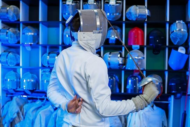 Молодой парень в костюме фехтовальщика с мечом в руке, на синем фоне, неоновый свет. спортсмен тренируется. спорт, молодость, здоровый образ жизни. выборочный фокус
