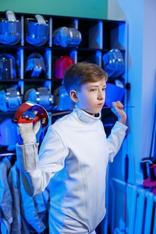 Молодой парень в костюме фехтовальщика с мечом в руке, на синем фоне, неоновый свет. спортсмен тренируется. спорт, молодость, здоровый образ жизни.