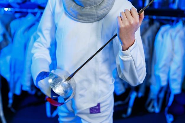 剣を手に、青い背景、ネオンの光でフェンシングスーツを着た若い男。アスリートはトレーニングします。スポーツ、若者、健康的なライフスタイル。