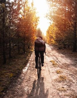ヘルメットをかぶった若い男は、日没時に秋の森のトレイルで砂利自転車に乗る。アクティブなライフスタイル。
