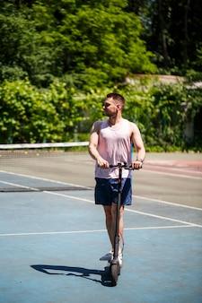 Tシャツとショートパンツを着た若い男が公園で電動スクーターに乗る