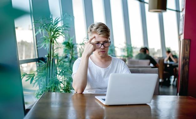 Молодой парень в белой футболке и очках работает на ноутбуке, сидя за столиком в кафетерии