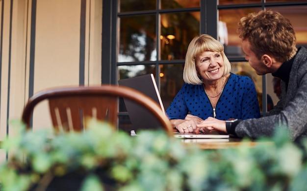 正装の若い男がカフェで老婆と商談。